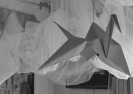 básně zavěšené nad postelí v atelieru